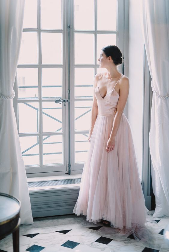 a blush wedding dress with a fitting silk bodice on spaghetti straps and a layered tulle skirt with train