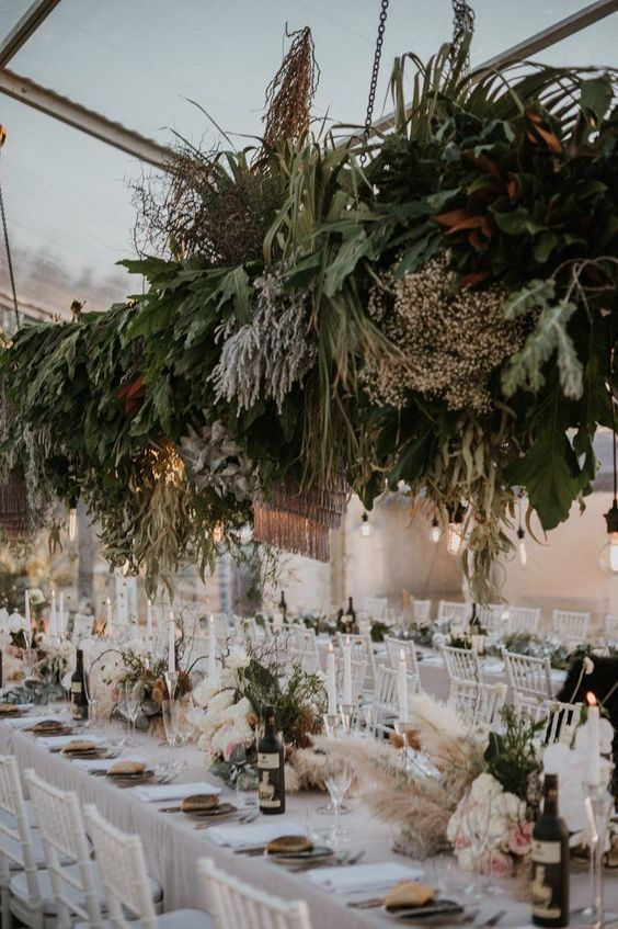 a boho wedding venue with a greenery and grass installation, greenery and pampas grass decor and candles