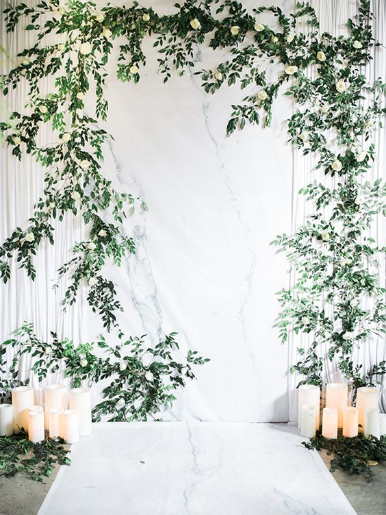a botanical wedding backdrop - a white marble one, with greenery and white blooms and pillar candles on the floor