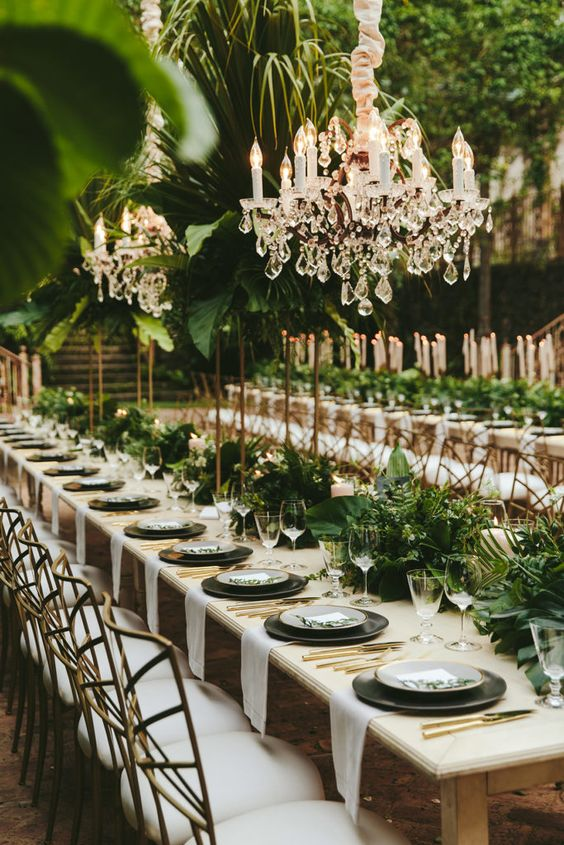 a botanical wedding reception space with chandeliers, lush textural greenery arrangements on the tables and over the space