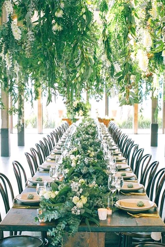 a botanical wedding reception space with hanging greenery and blooms and a greenery runner with blooms and candles