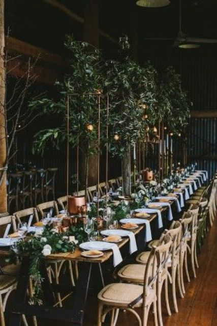 a botanical wedding venue with greenery on stands, greenery runners, candles and lights looks pretty