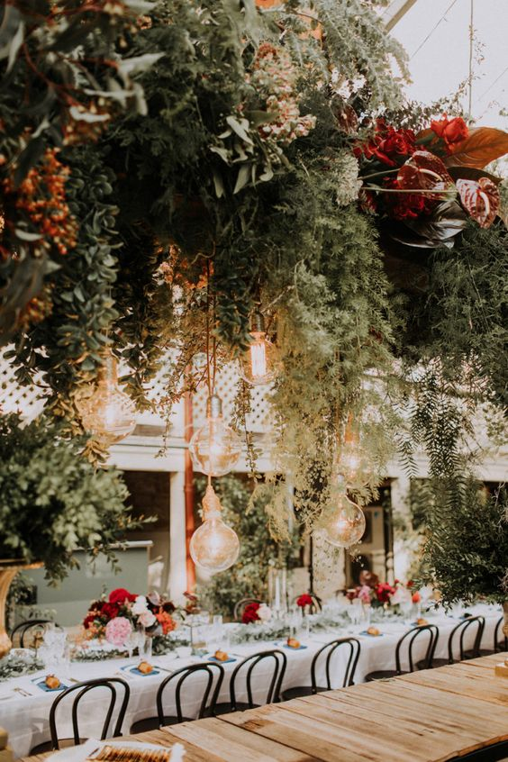 a botanical wedding venue with lush greenery, bright blooms and leaves all over the space looks amazing