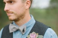 a chambray shirt, a woolen waistcoat and a printed bow tie plus a succulent boutonniere for a rustic groom's look