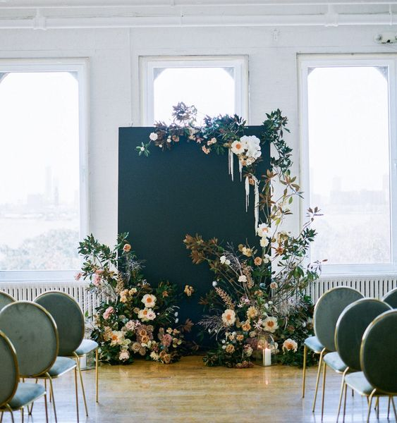 a chic and refined wedding backdrop of peachy and blue blooms, greenery, foliage, dried and fresh elements and a black canvas