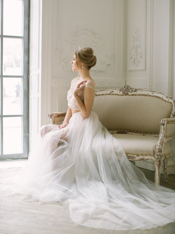 a chic bridal spearate with an embellished blush crop top and a white layered tulle skirt with a train