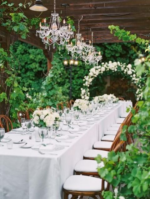 a chic greenery wedding reception space with white florals, a white floral arch and crystal chandeliers is chic