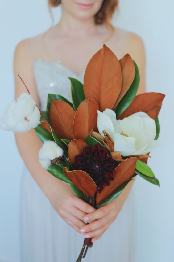 a chic wedding bouquet of magnolia blooms and leaves, burgundy blooms and cotton