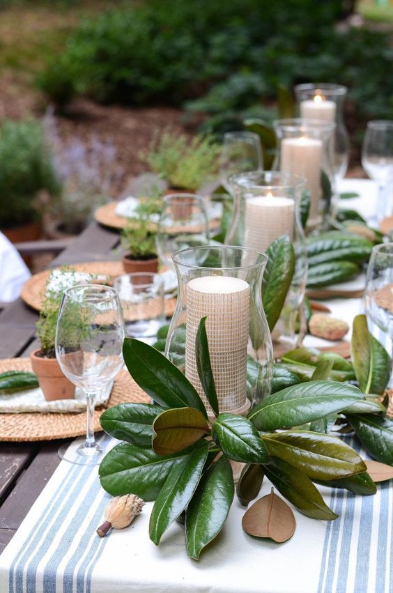 a cool wedding tablescape with a striped runner, a magnolia leaf and candle centerpiece and wicker chargers