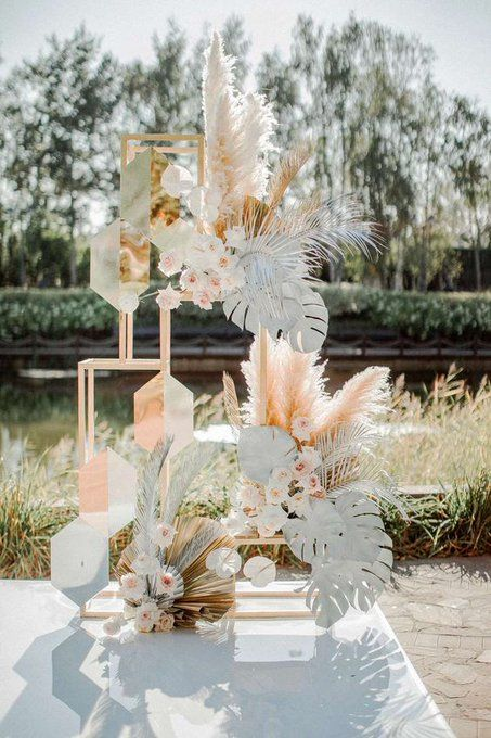 a creative botanical wedding backdrop of pampas grass, white monstera leaves, dried fronds and geometric details is wow