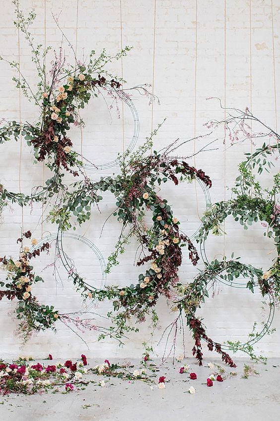 a creative wedding backdrop of metal hoops with greenery and moody blooms is ideal for a fall wedding