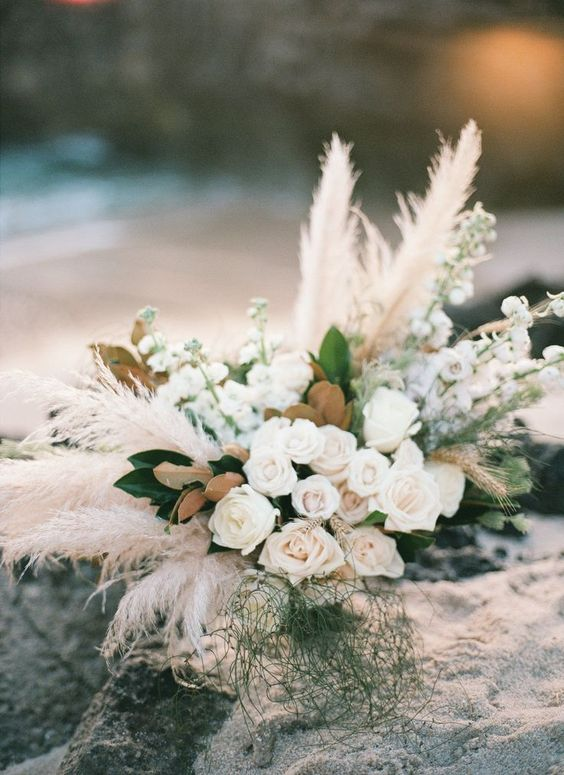 a dimensional and textural wedding centerpiece of blush roses, pampas grass and magnolia leaves