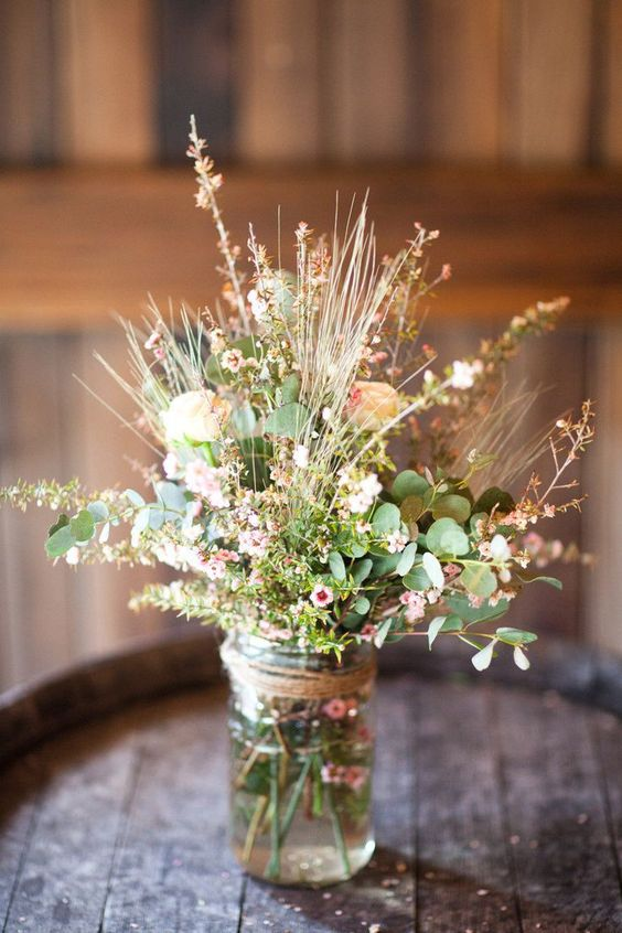 a farmhouse wedding centerpiece of a jar wrapped with twine, with greenery and waxflower is a lovely idea for a summer wedding