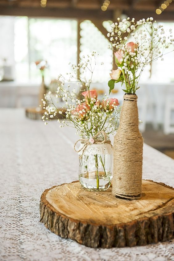 a farmhouse wedding centerpiece of a wood slice, a jar and a bottle wrapped with twine, with baby's breath and pink roses