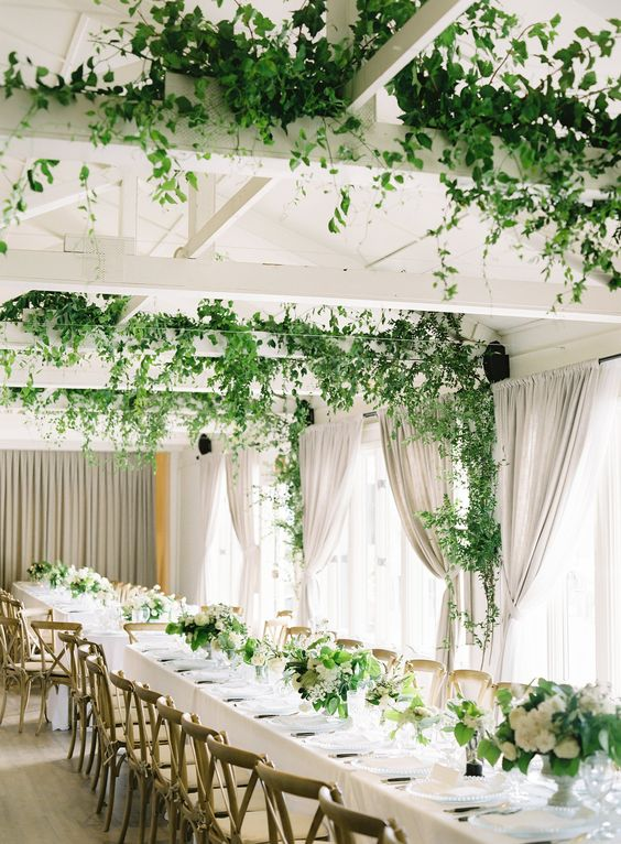 a fresh and enlivened wedding reception space with greenery on the beams, white floral and greenery centerpieces looks cool