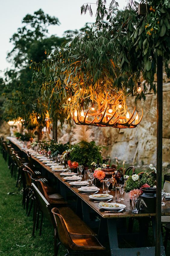 a fresh botanical wedding venue with a greenery installation with antler chandeliers, greenery and floral centerpieces
