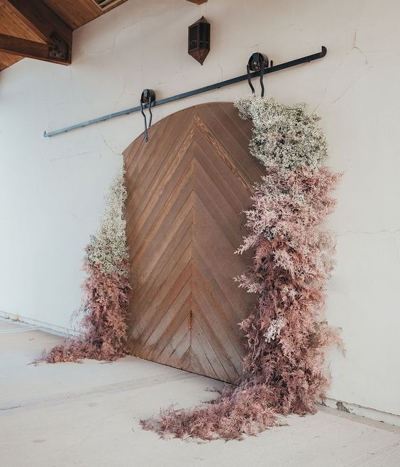 a gorgeous botanical wedding backdrop of a barn door and ombre grasses and baby's breath is amazing