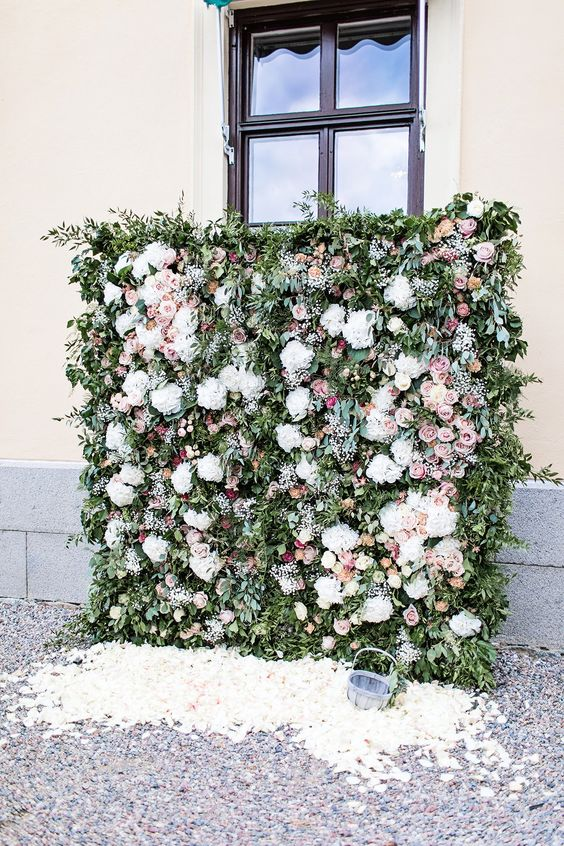 a gorgeous botanical wedding backdrop of greenery, white, mauve and pink blooms and lots of foliage plus petals on the ground
