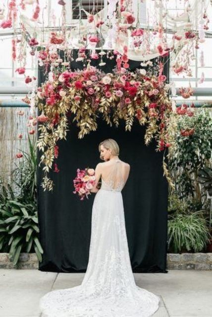 a gorgeous wedding backdrop of a black canvas, gilded foliage and leaves, pink, red, mauve and blush blooms and hanging flowers overhead
