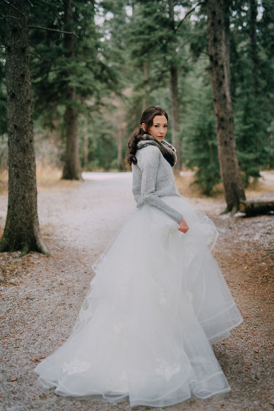 a grey comfy sweater over a princess style wedding dress and a faux fur scarf looks very contrasting