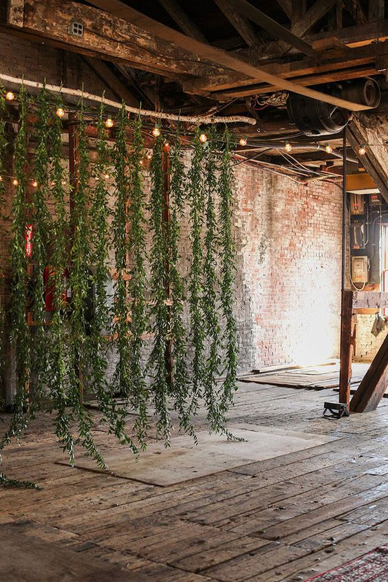 a hanging greenery backdrop with lights will soften the industrial space and make it look inspiring and fresh