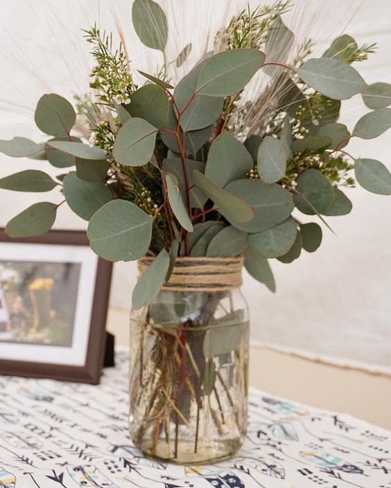 a jar wrapped with twine, with waxflower and eucalyptus is a very lovely idea for a rustic wedding and is easy to compose