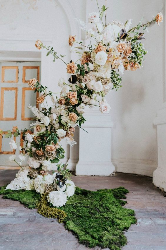a jaw-dropping wedding backdrop of blush, white and peachy blooms, greenery and moss on the floor gives a garden feel to the space