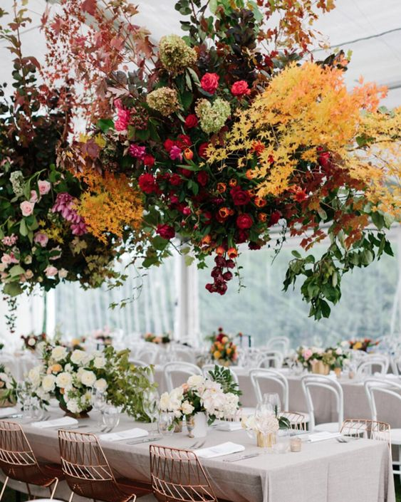 a jaw-dropping wedding venue with white blooms on the table and colorful floral hanging decorations is amazing