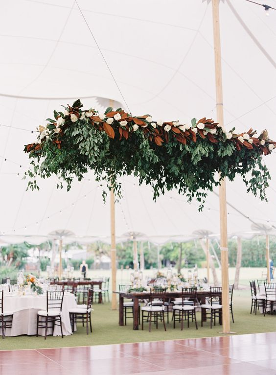 a large wedding decoration of greenery and magnolias is a cool way to accent your dance floor