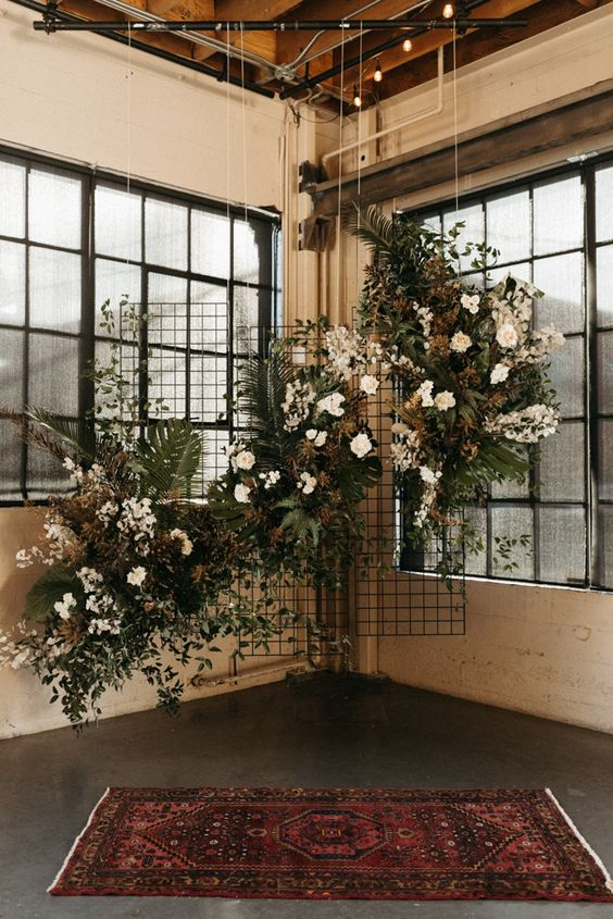 a lovely dried wedding backdrop of foliage, greenery, white and blush blooms and lot sof dried touches to enliven the space