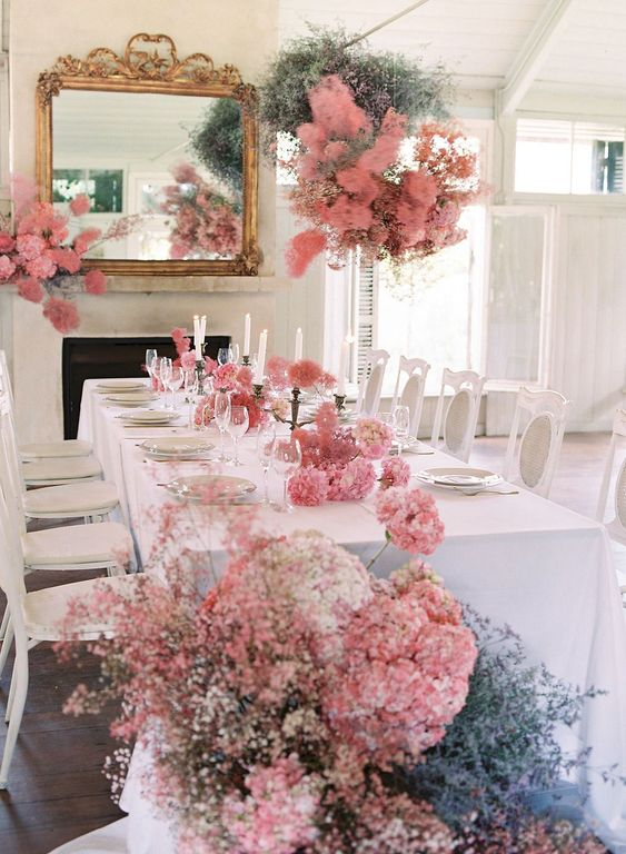 a lovely wedding reception space fully decorated with pink smokebush and with blue blooms