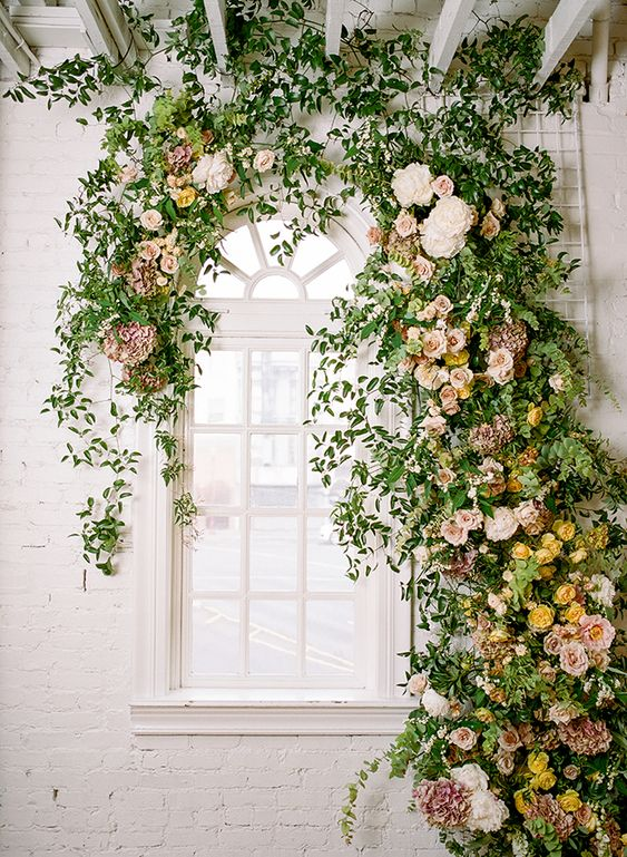 a lush and beautiful floral and greenery indoor wedding backdrop is a lovely and chic idea for a refined space