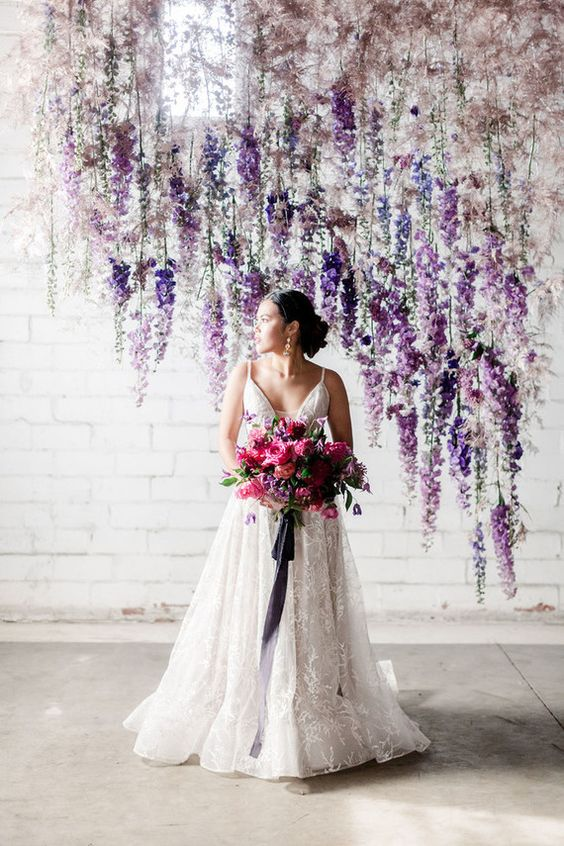 a lush floral wedding backdrop with an ombre effect from blush and mauve to lavender and purple hanging over the space