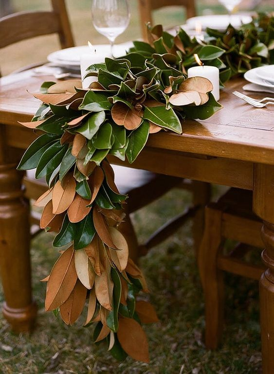 a lush magnolia leaf wedding table garland with candles on an uncovered table is a chic and bold idea