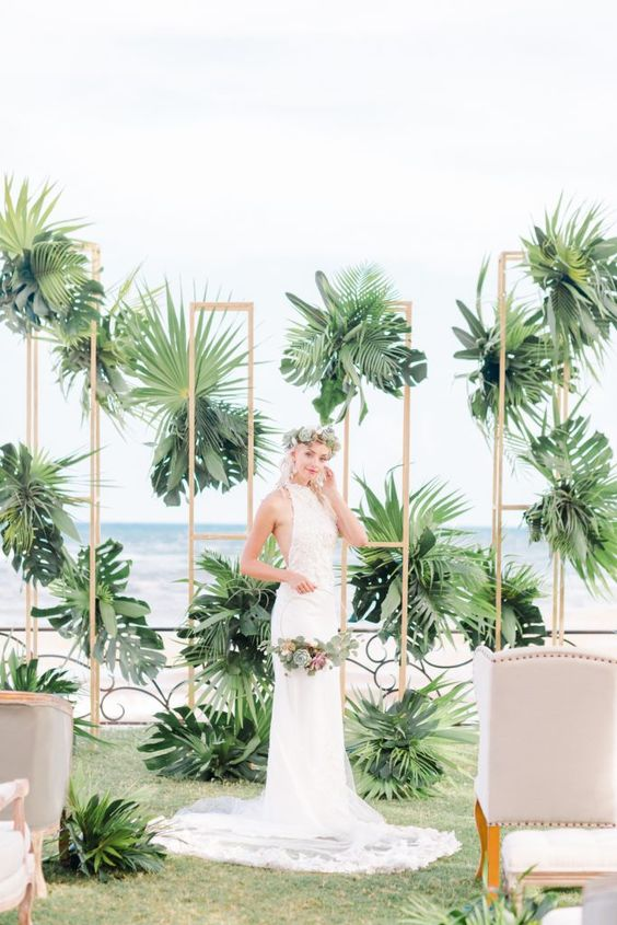 a lush tropical wedding backdrop of plywood with lots of tropical leaves and a sea view is ideal for a tropical wedding