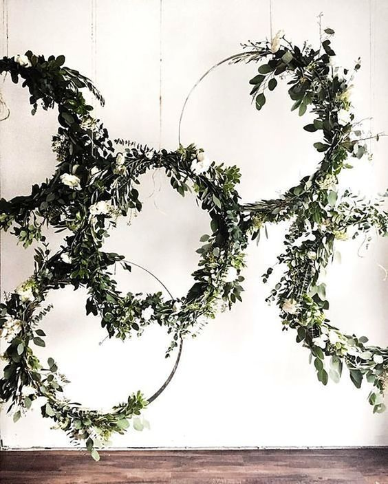 a lush wedding backdrop of embroidery hoops with white blooms and greenery is a chic and lovely idea to rock