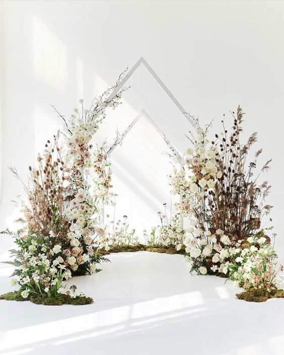 a lush wedding backdrop of white and blush blooms, dried herbs and leaves, greenery and triangle arches over the space