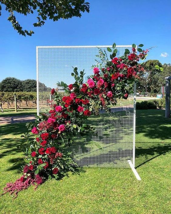 a mesh wedding backdrop with lots of greenery, fuchsia, pink and burgundy blooms attached is a stunning and bold idea