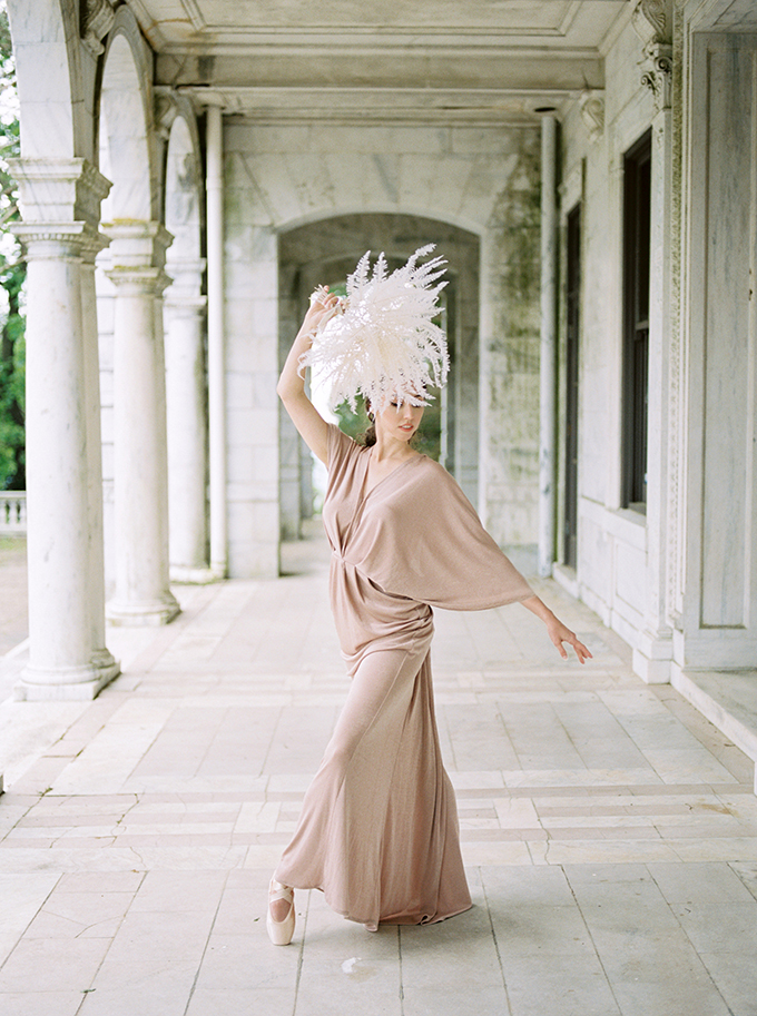 a modern ballet wedding dress in dusty pink, with a deep neckline, wide sleeves and a draped skirt
