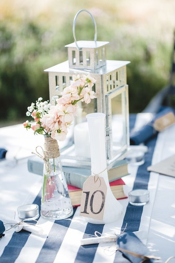 a nautical wedding centerpiece of a candle lantern, a bottle with pink blooms wrapepd with twine and a vase with a table number