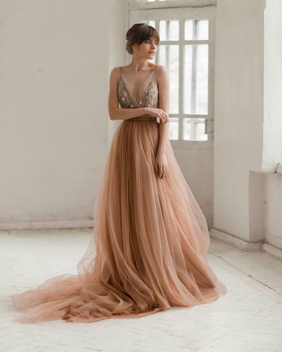 a peachy pink wedding dress with a fitting floral embroidery bodice on spaghetti straps and a layered tulle skirt with a train