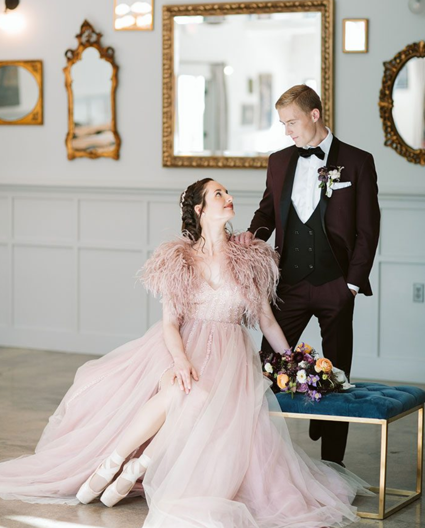 a pink A line wedding dress with a beaded bodice, a V neckline, a layered skirt and a feather coverup