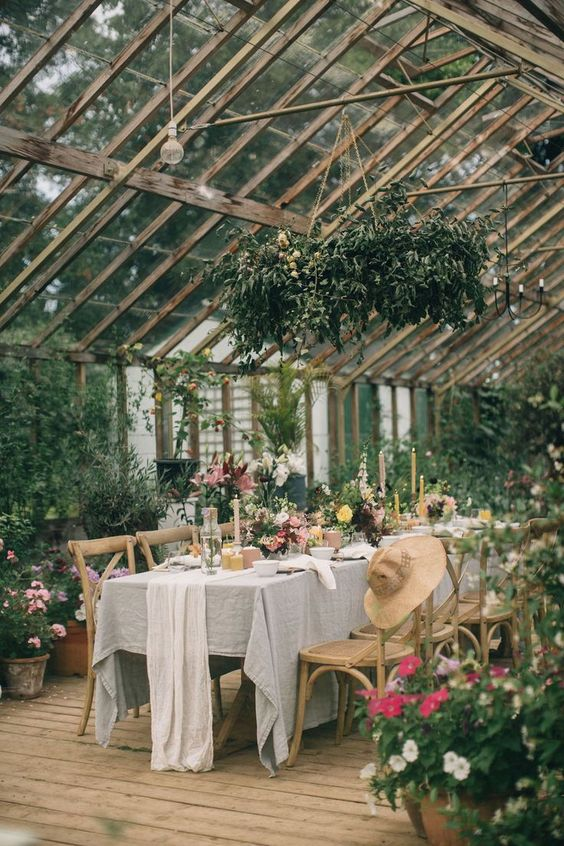 a pretty garden wedding venue with potted greenery and blooms, a greenery chandelier and bright blooms on the table