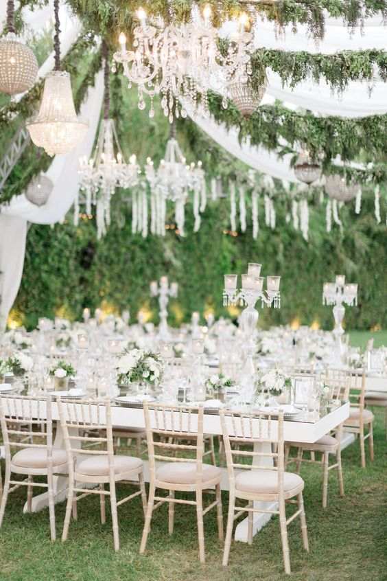 a refined wedding reception with grass and greenery walls, greenery garlands and crystal chandeliers and candles looks chic
