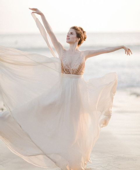 a romantic rose gold wedding dress with a sleeveless sequin bodice and a deep neckline plus a layered skirt