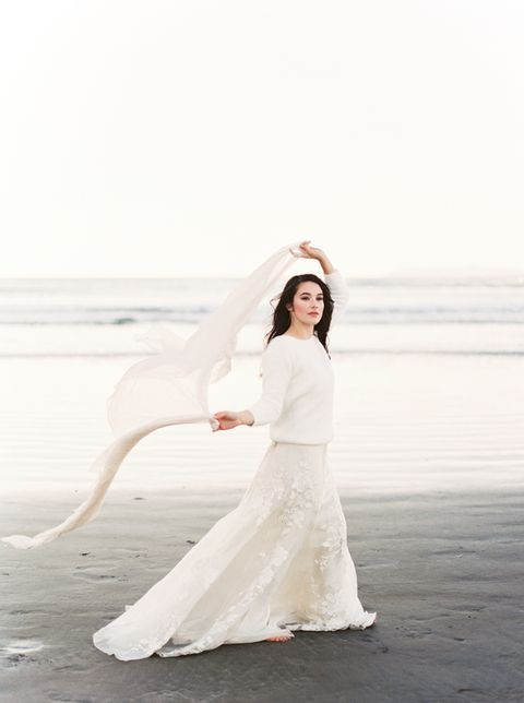a romantic white lace dress and a white chunky knit sweater for a winter coastal bride