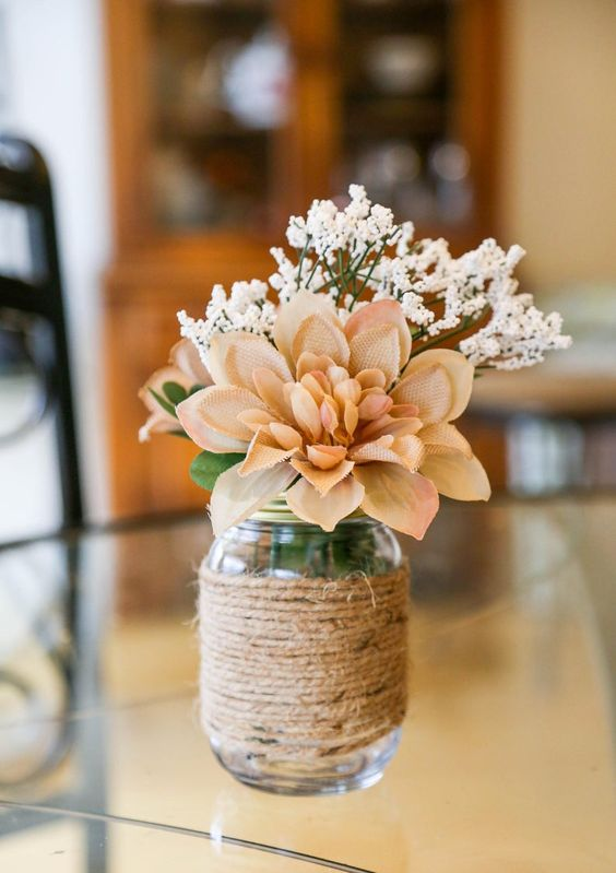 a rustic wedding centerpiece of a jar wrapped with twine, a burlap bloom and a branch of faxu baby's breath is cool