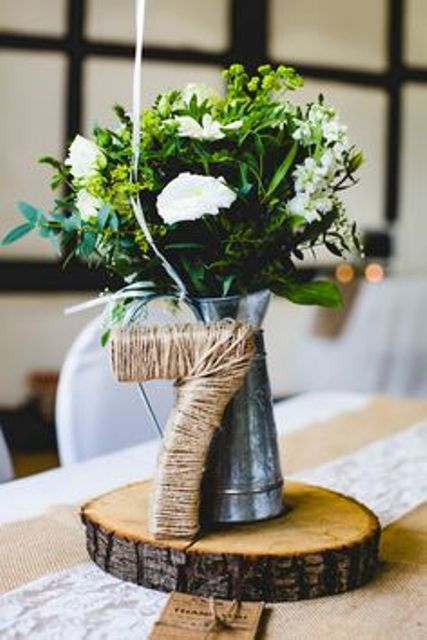 a rustic wedding centerpiece of a wood slice, greenery and white blooms in a metal jug and a twine wrapped table number