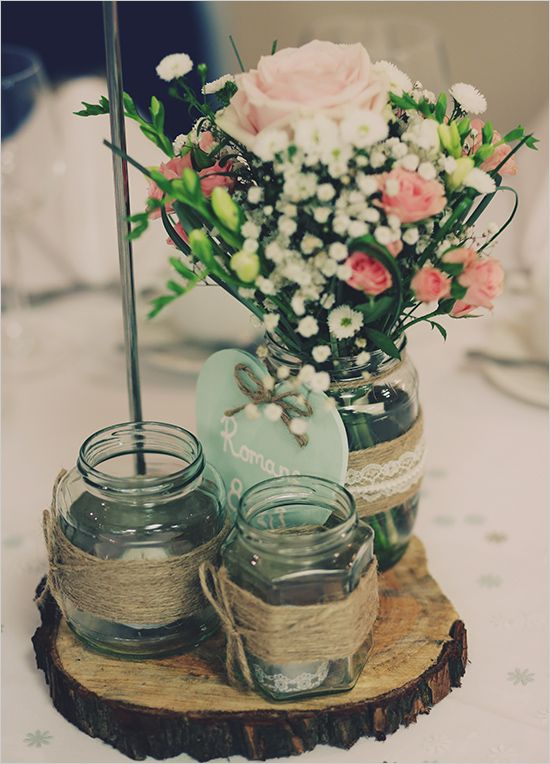 a rustic wedding centerpiece of a wood slice, jars with twine, candles, an arrangement of baby's breath and pink blooms