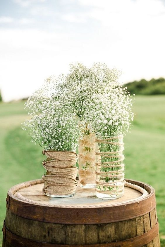 a rustic wedding centerpiece of vases wrapped with twine and burlap, with baby's breath is a lovely idea for a farmhouse wedding